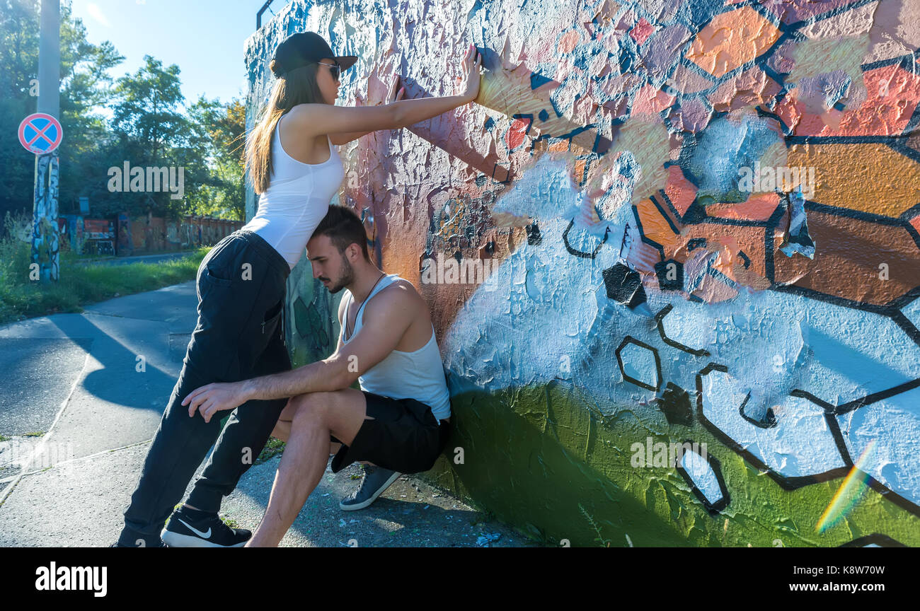 A young HipHop styled couple standing against a wall in a urban environment. - Stock Image