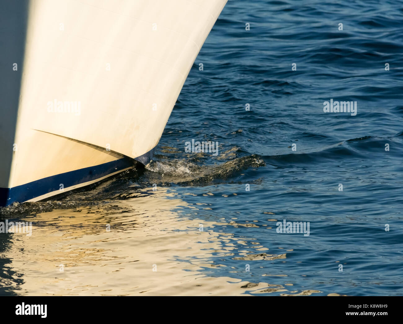 The hull of a white boat with a blue stripe cuts slowly through the water with  the white reflecting of the myriad - Stock Image