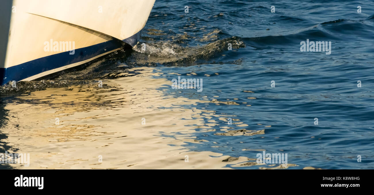 A small wave shows how the white hull of a small boat cuts through small ripples in the water surface. - Stock Image