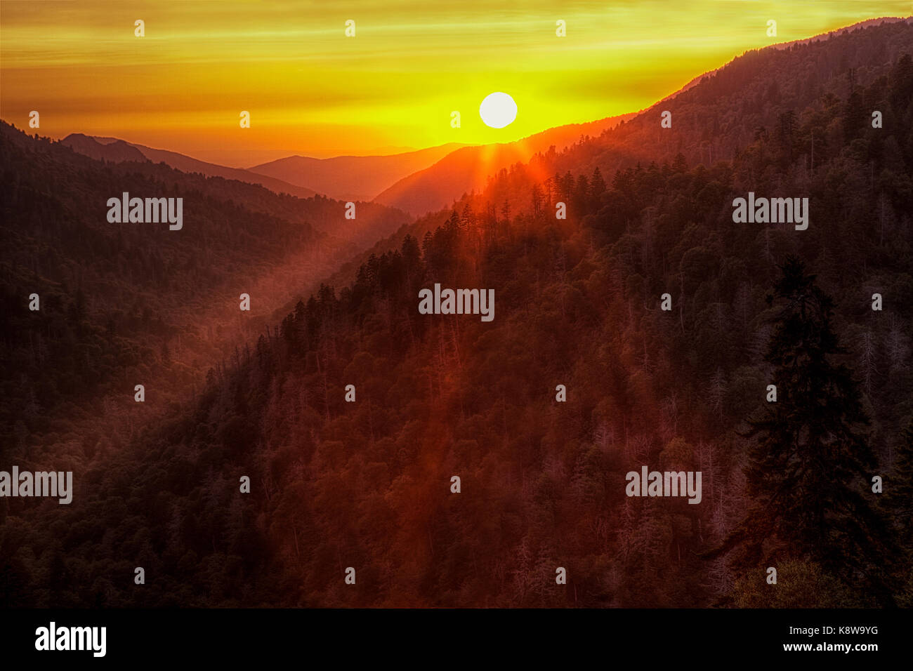 The setting sun sends its warm rays over the mountainsides at the Morton Overlook in the Great Smoky Mountains National - Stock Image
