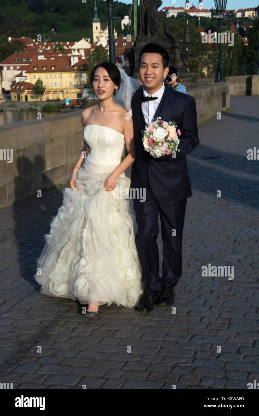 Chinese wedding couple taking advantage of the early morning quiet for their photo shoot on the Charles Bridge (Karluv - Stock Image