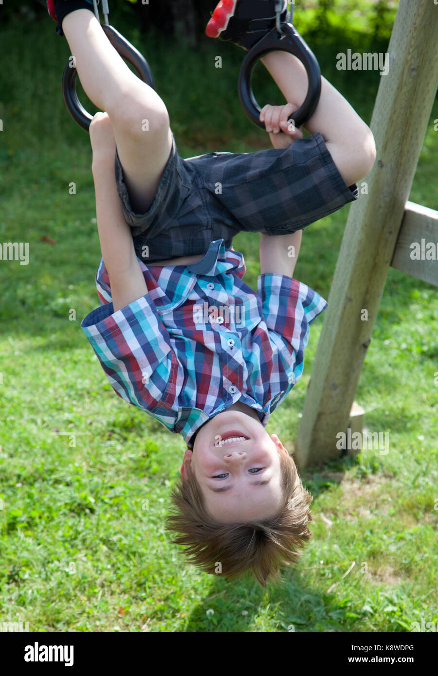 a smiling brown haired boy grins as he hangs upside down on rings on a swing set outside - Stock Image