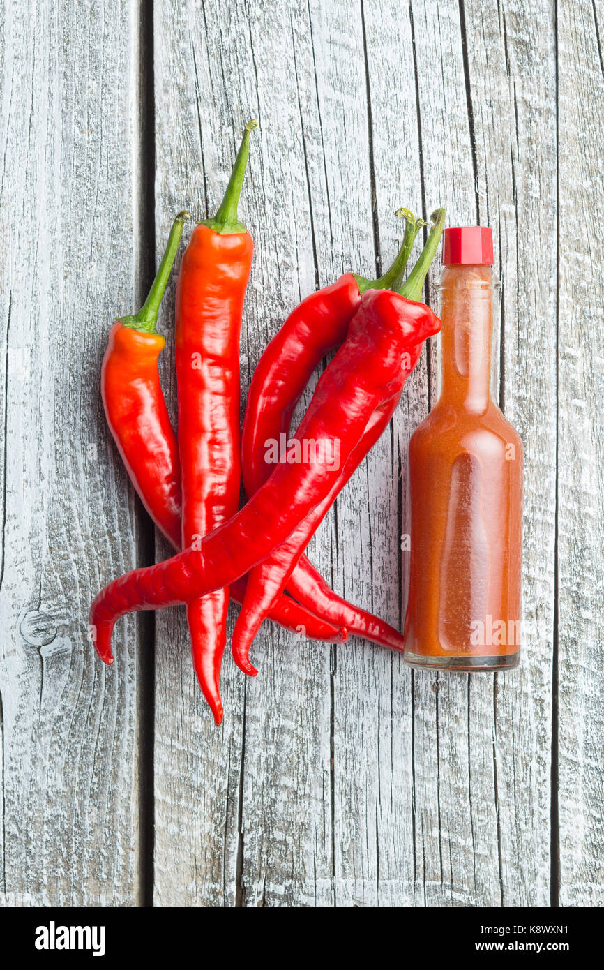 Red chili peppers and chili sauce. Top view. - Stock Image
