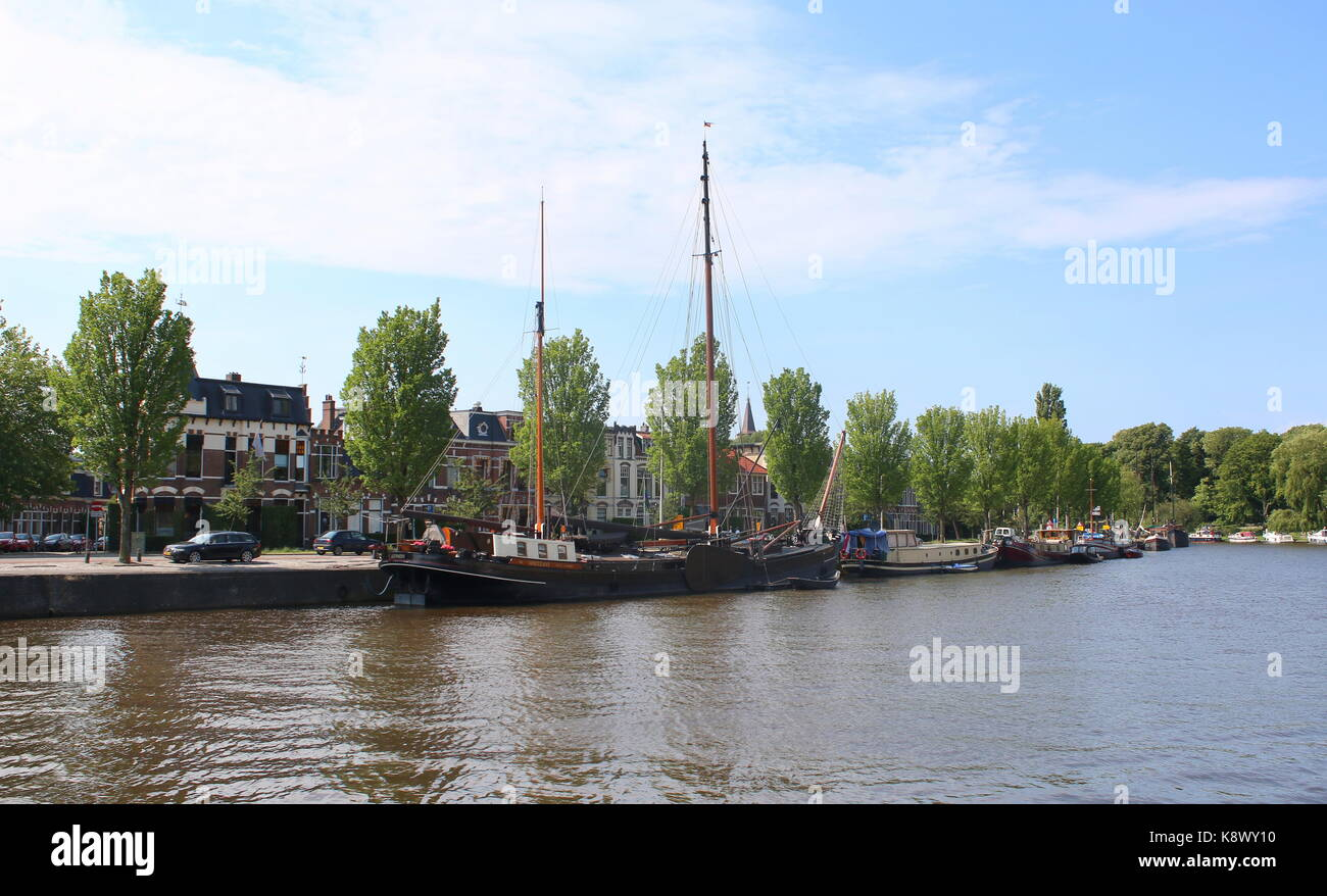 Traditional sailing ships moored along Westersingel canal or Westerstadsgracht (Western canal) in downtown Leeuwarden, - Stock Image