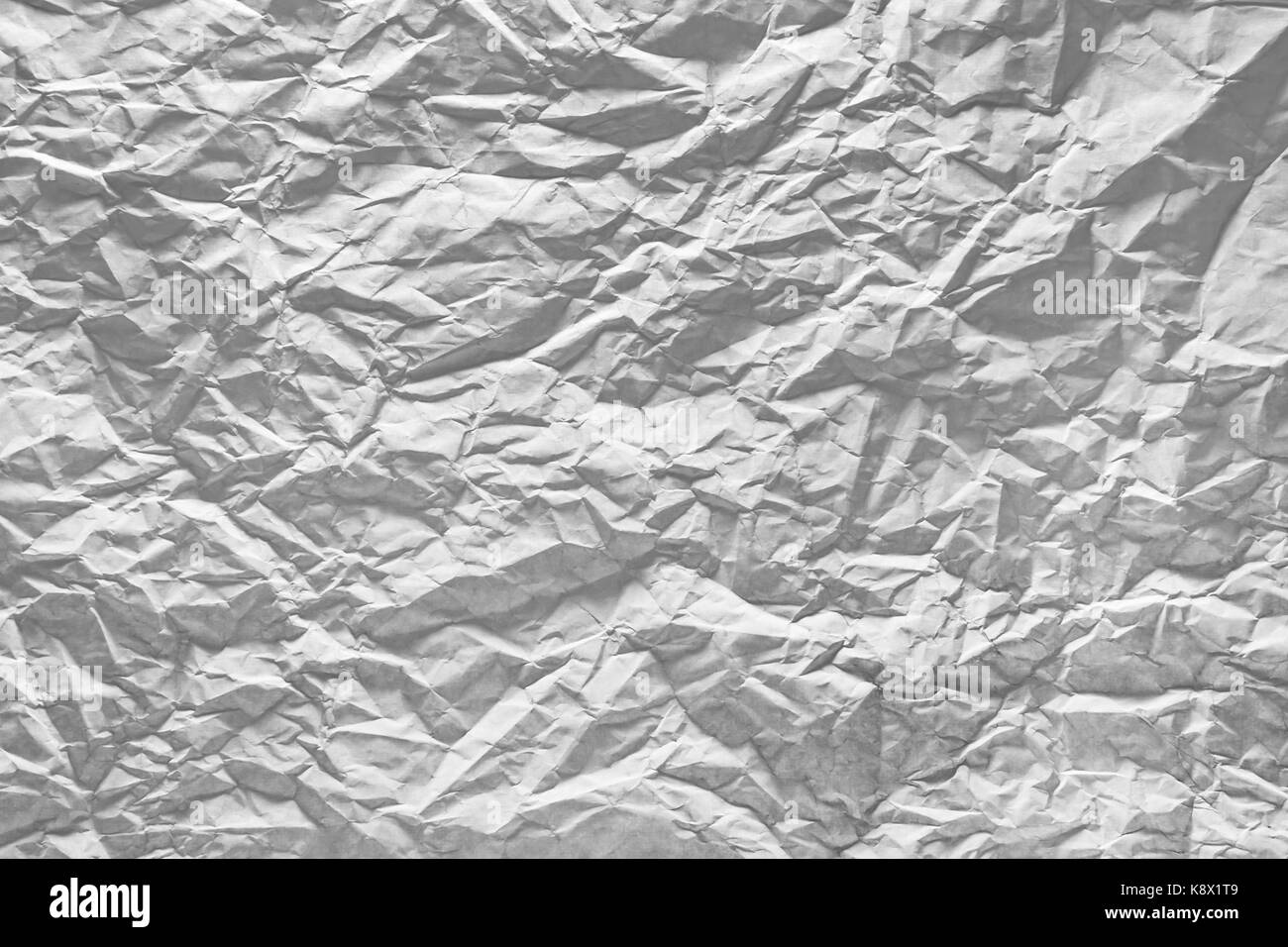Surface of crumpled paper highlighted by light. Stressed, illuminated sheet of paper paper. - Stock Image