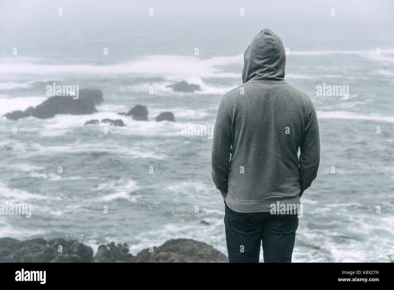 Sad and lonely man standing in front of the pacific ocean and looking at the stormy sea on Vancouver Island. - Stock Image