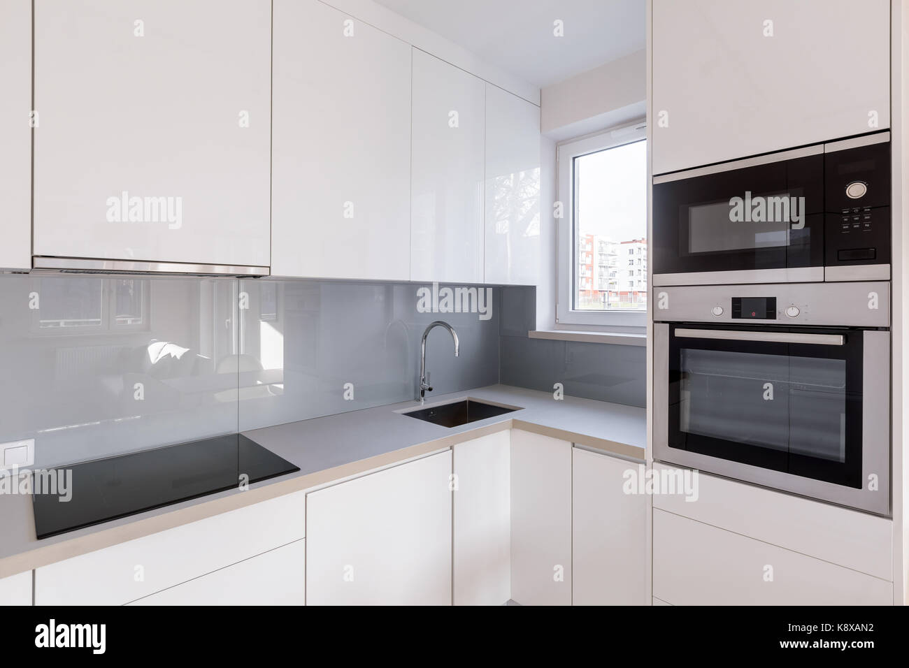 Modern kitchen with white cupboards, high gloss tiles and new