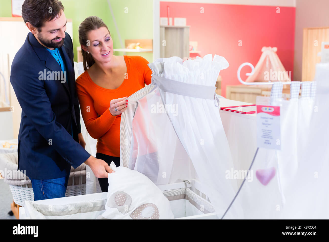 a18bd1612 Couple expecting baby buying children bed in store Stock Photo ...