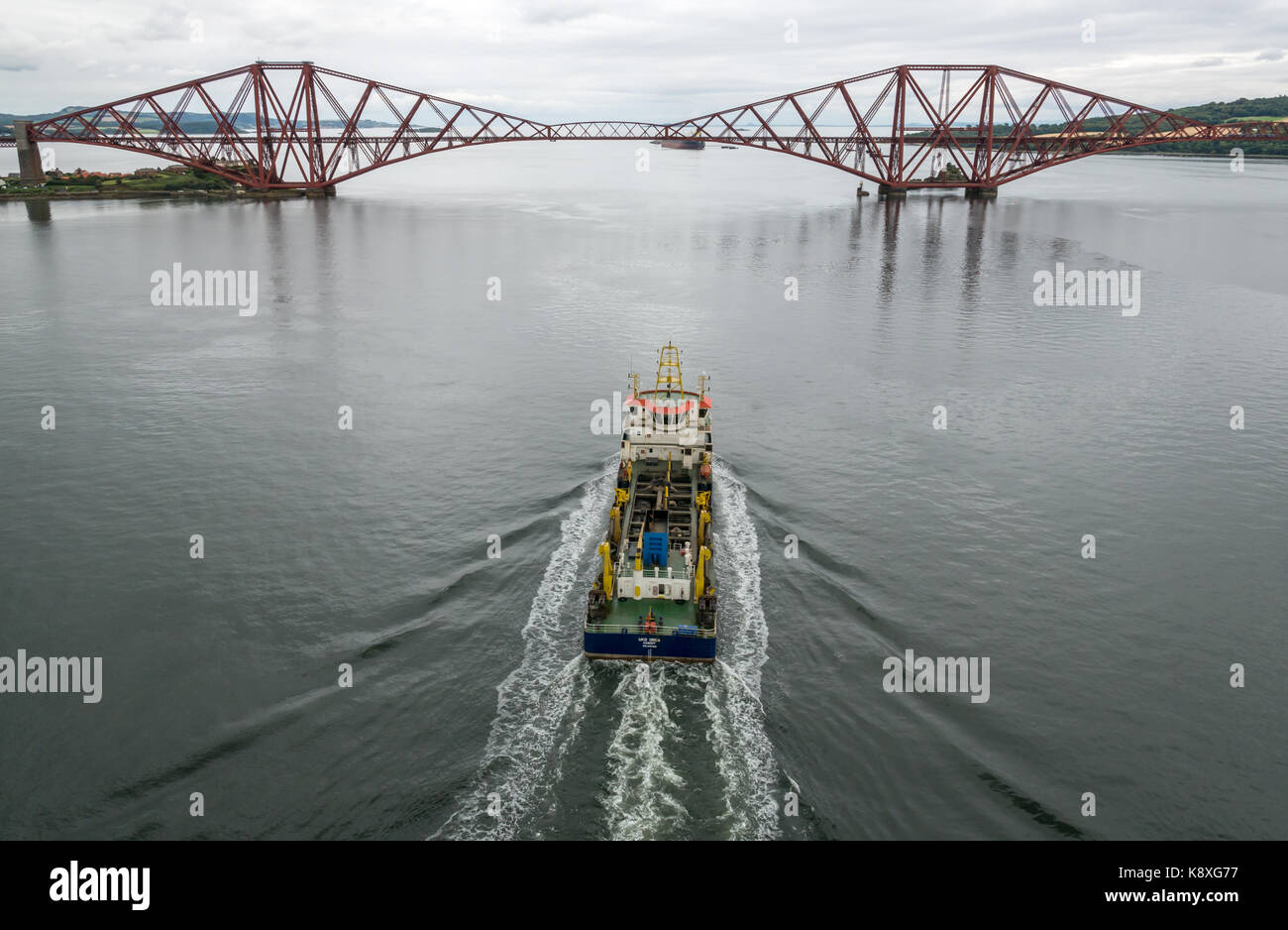 UKD Orca, a suction hopper dredger sailing towards cantilever Forth Rail Bridge in calm water, Firth of Forth, Scotland, - Stock Image
