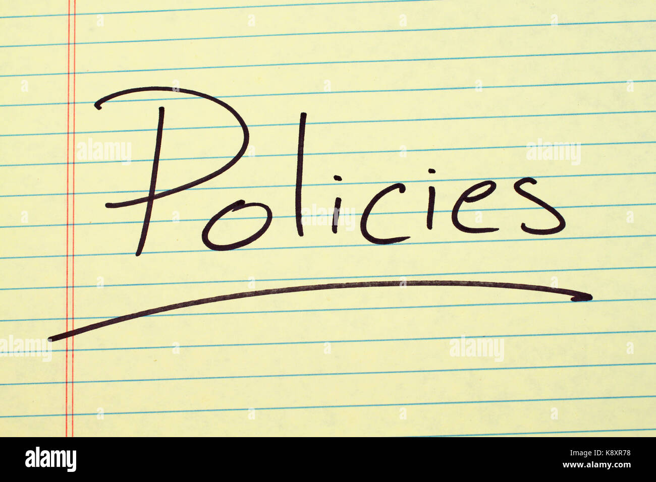 The word 'Policies' underlined on a yellow legal pad - Stock Image