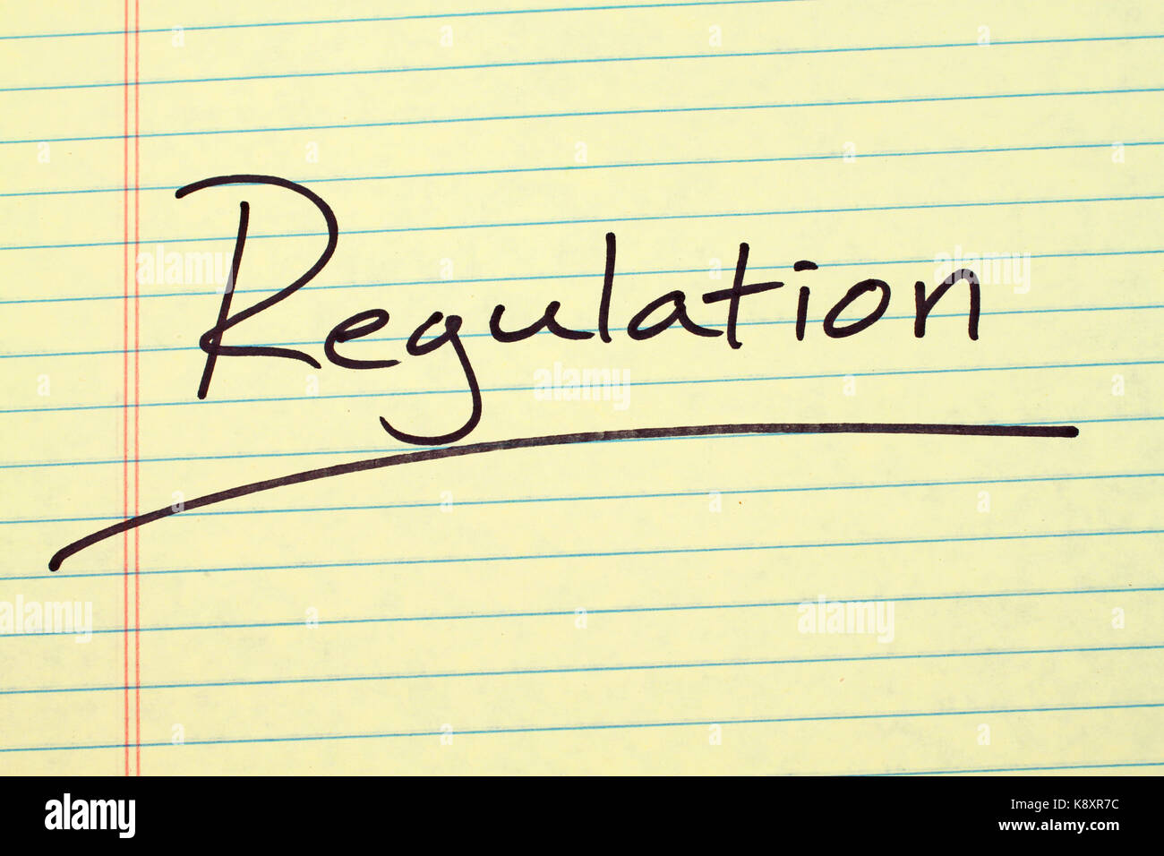The word 'Regulation' underlined on a yellow legal pad - Stock Image