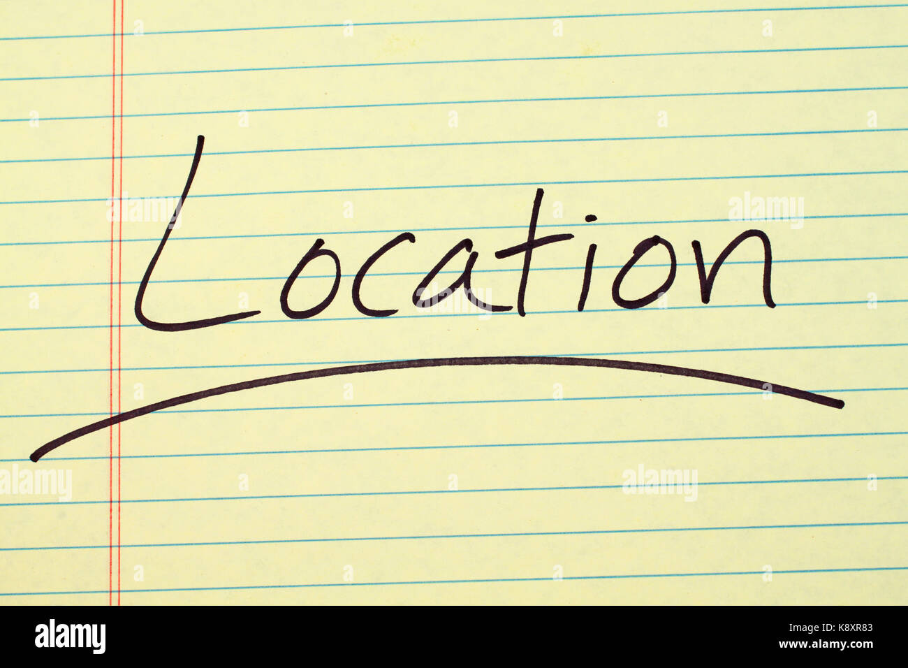 """The word """"Location"""" underlined on a yellow legal pad Stock Photo"""