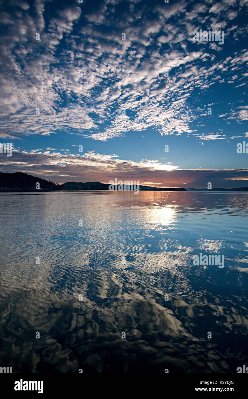 A striking inspirational blue sky cloudy salt water lake sunrise with cloud water reflections. Captured on Lake - Stock Image