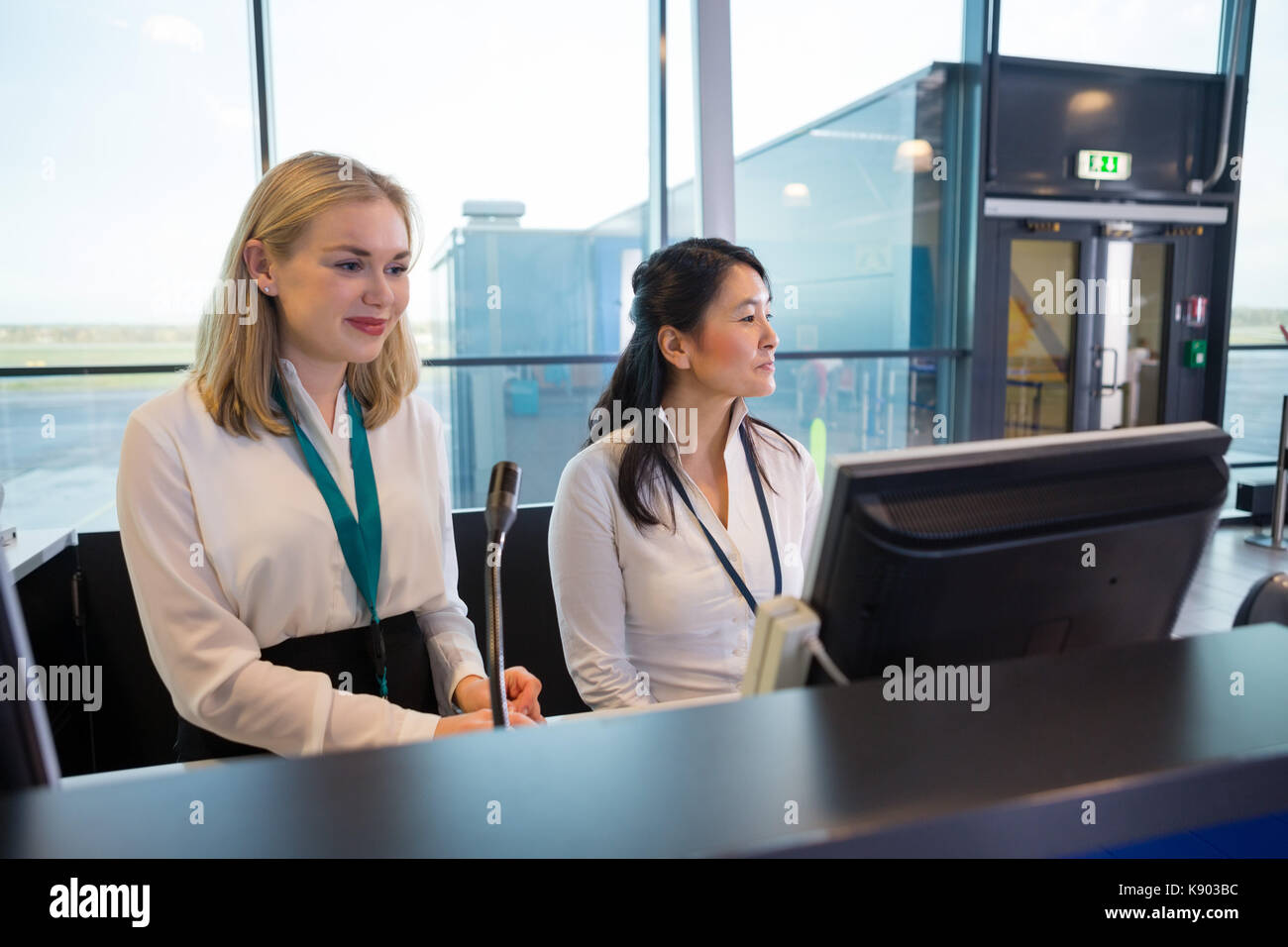 Receptionists Sitting At Help Desk In Airport - Stock Image