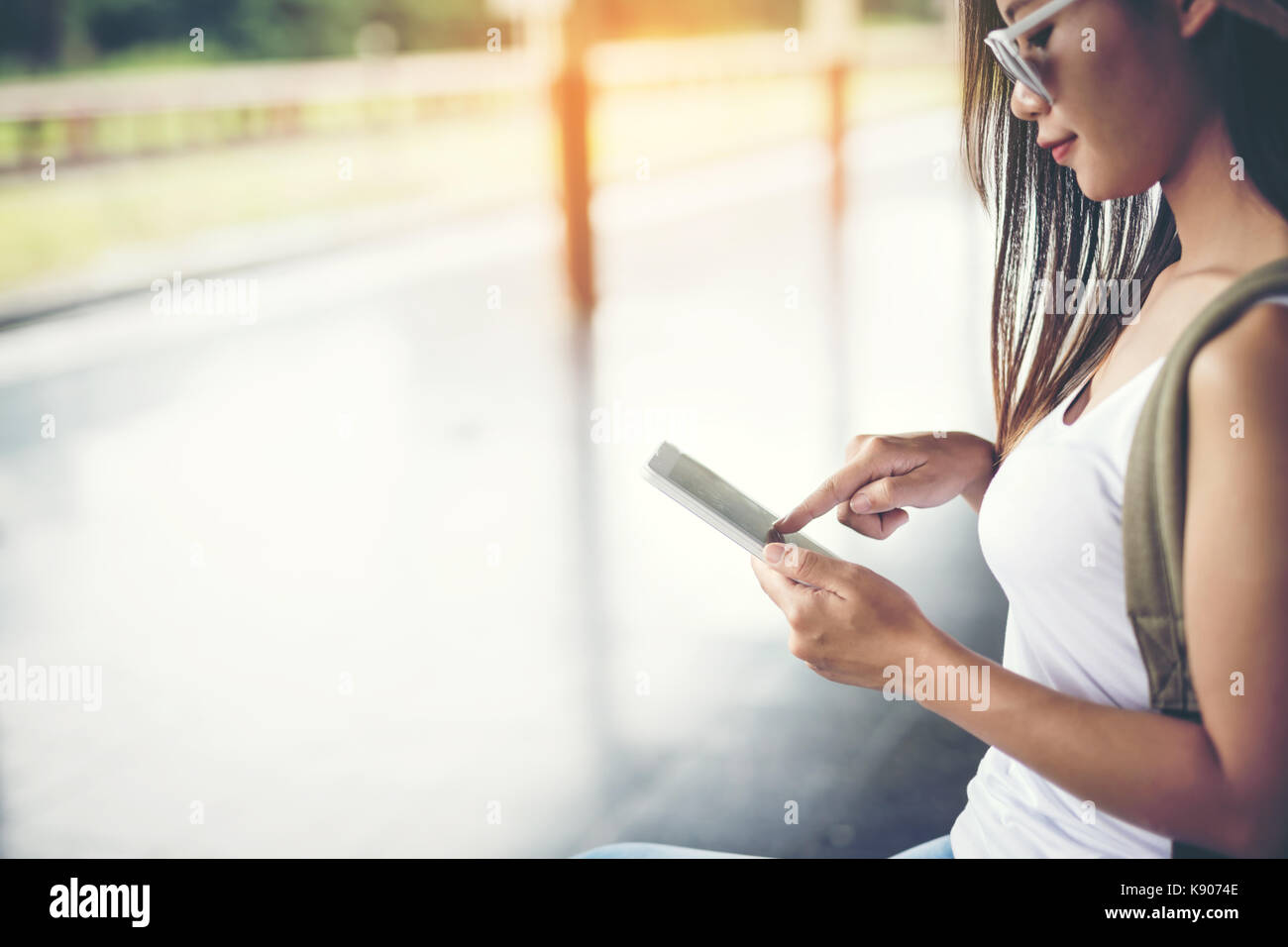 Happy female tourists in the train station on a mobile tablet.Travel concept. - Stock Image