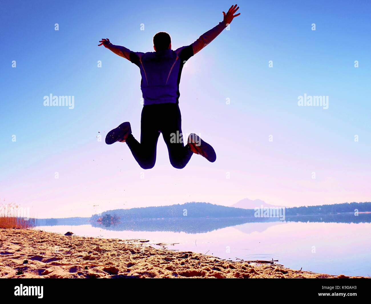 Man crazy jumping on beach.  Sportsman flying on beach during the amazing sunrise above horizon - Stock Image
