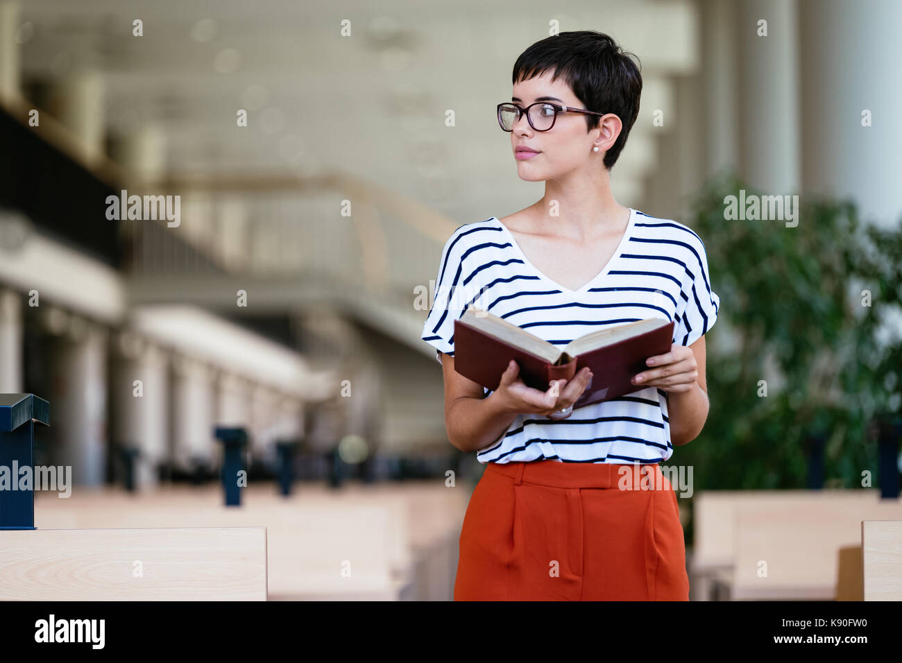 Portrait of young female student in library - Stock Image