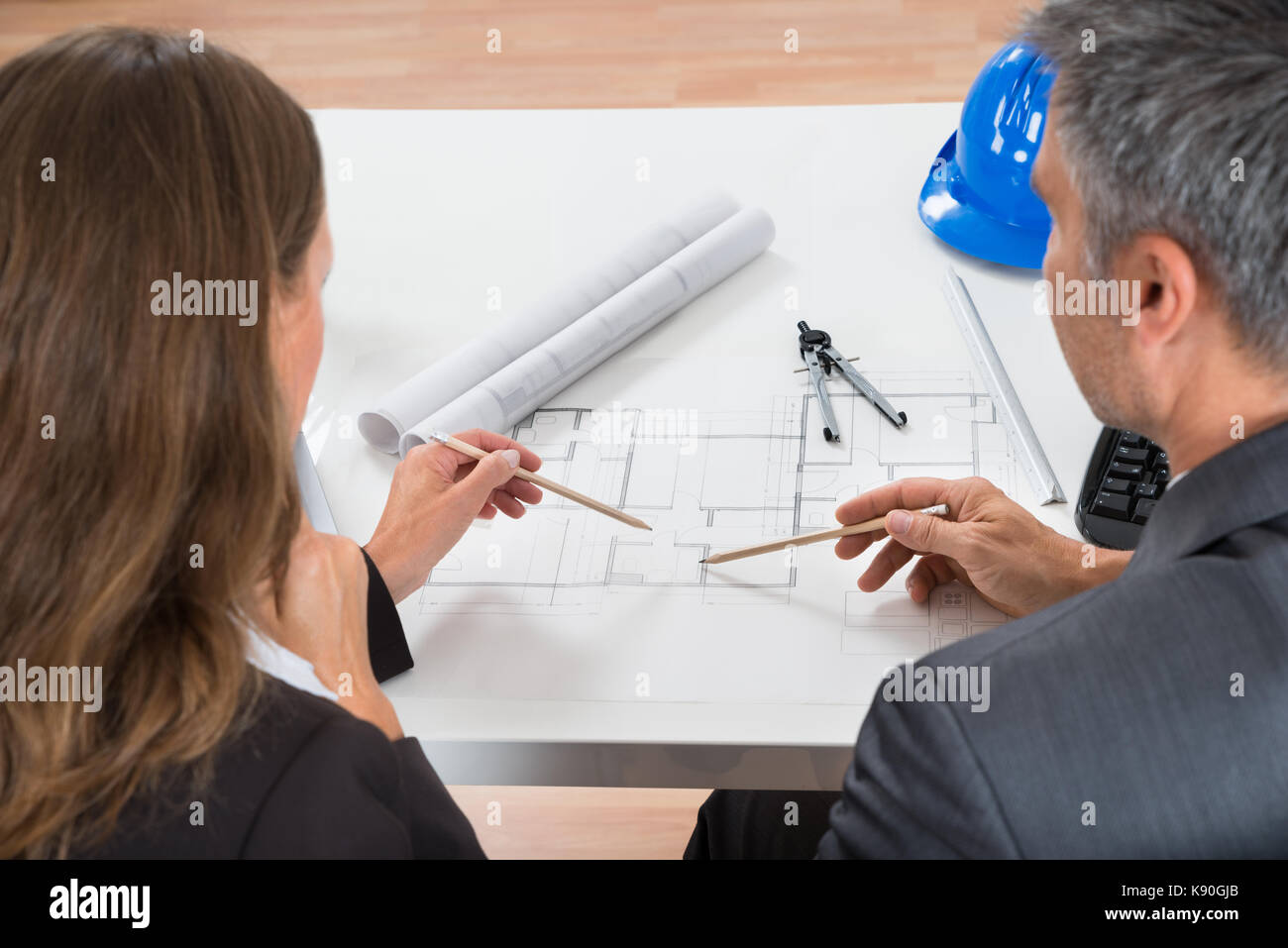 Close-up Of Two Businesspeople Working On Blueprint In Office - Stock Image