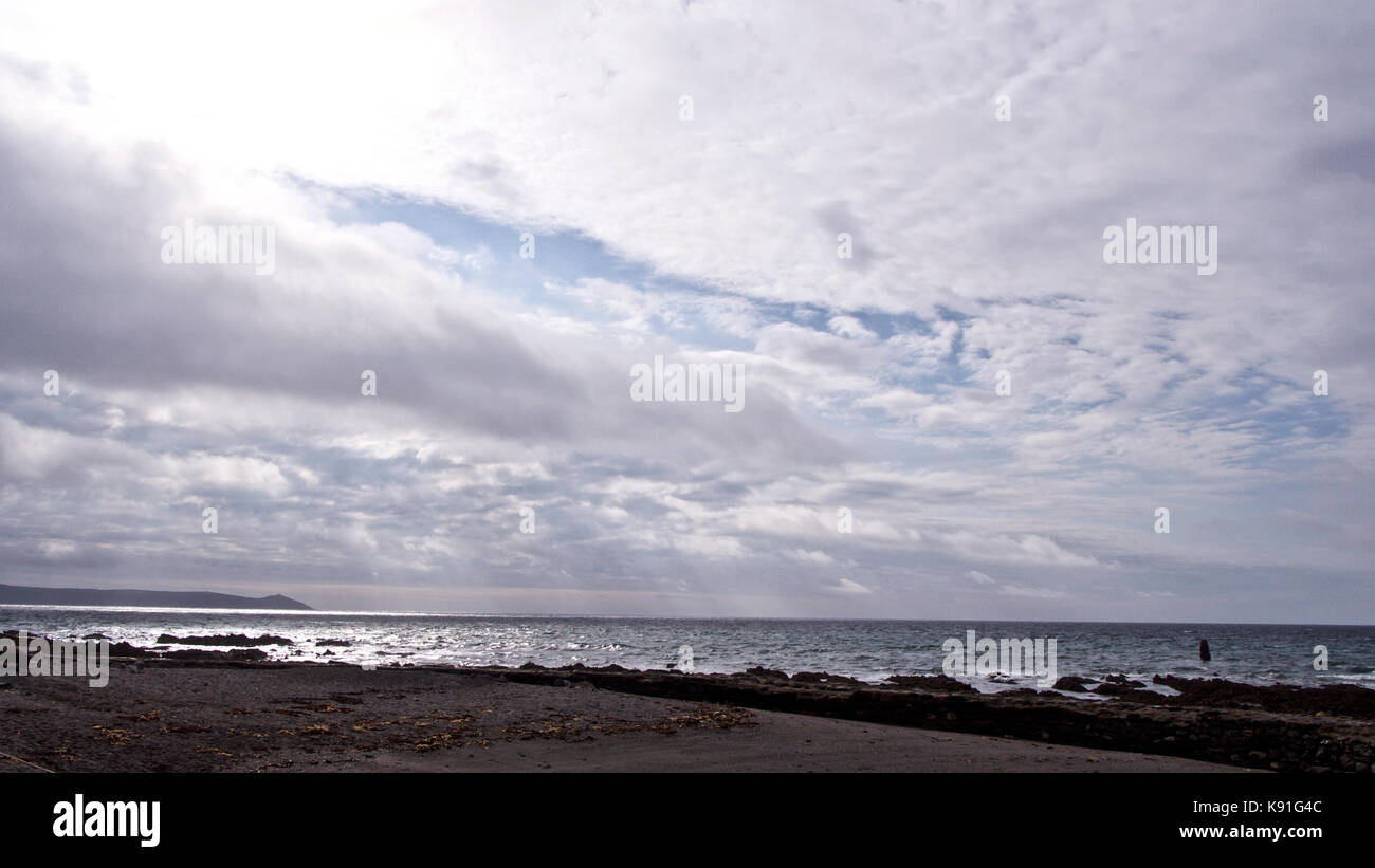 Sun coming through clouds and the beach - Stock Image