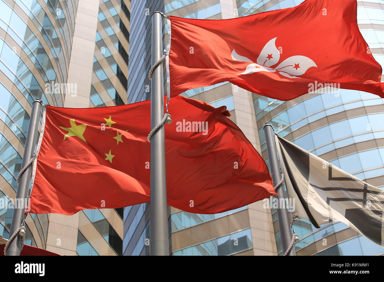 chinese and hong kong flags blow in the wind with glass building background - Stock Image