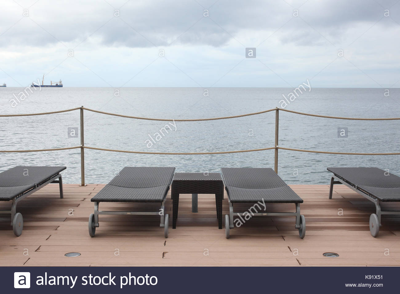 sunbeds on afront sea  wooden deck in an overcast day - Stock Image