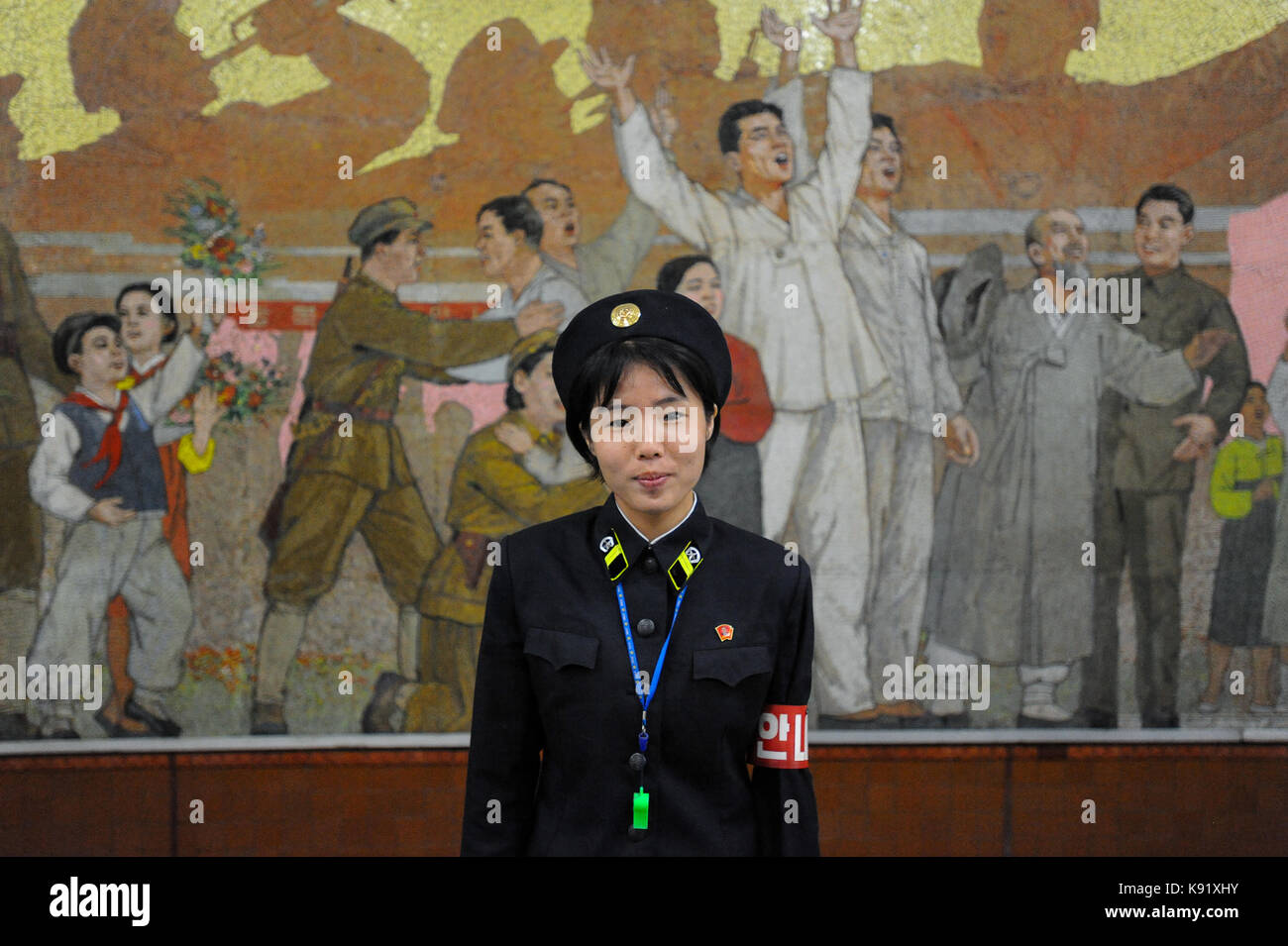 09.08.2012, Pyongyang, North Korea, Asia - A platform guard stands in front of a huge propaganda mural inside a - Stock Image
