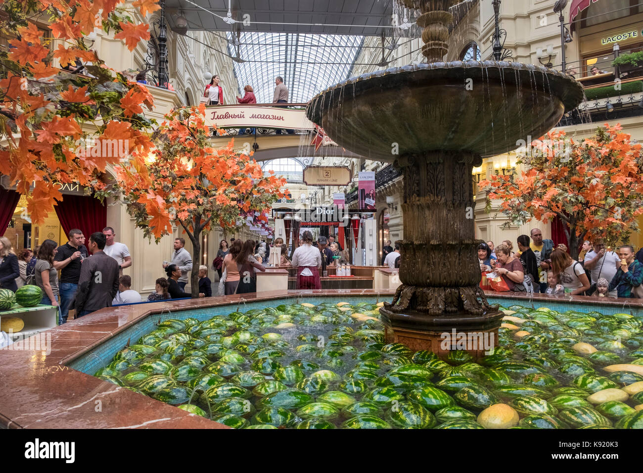 Interior detail of the upmarket GUM shopping mall, Red Square, Moscow, Russia, showing a water fountain filled with - Stock Image