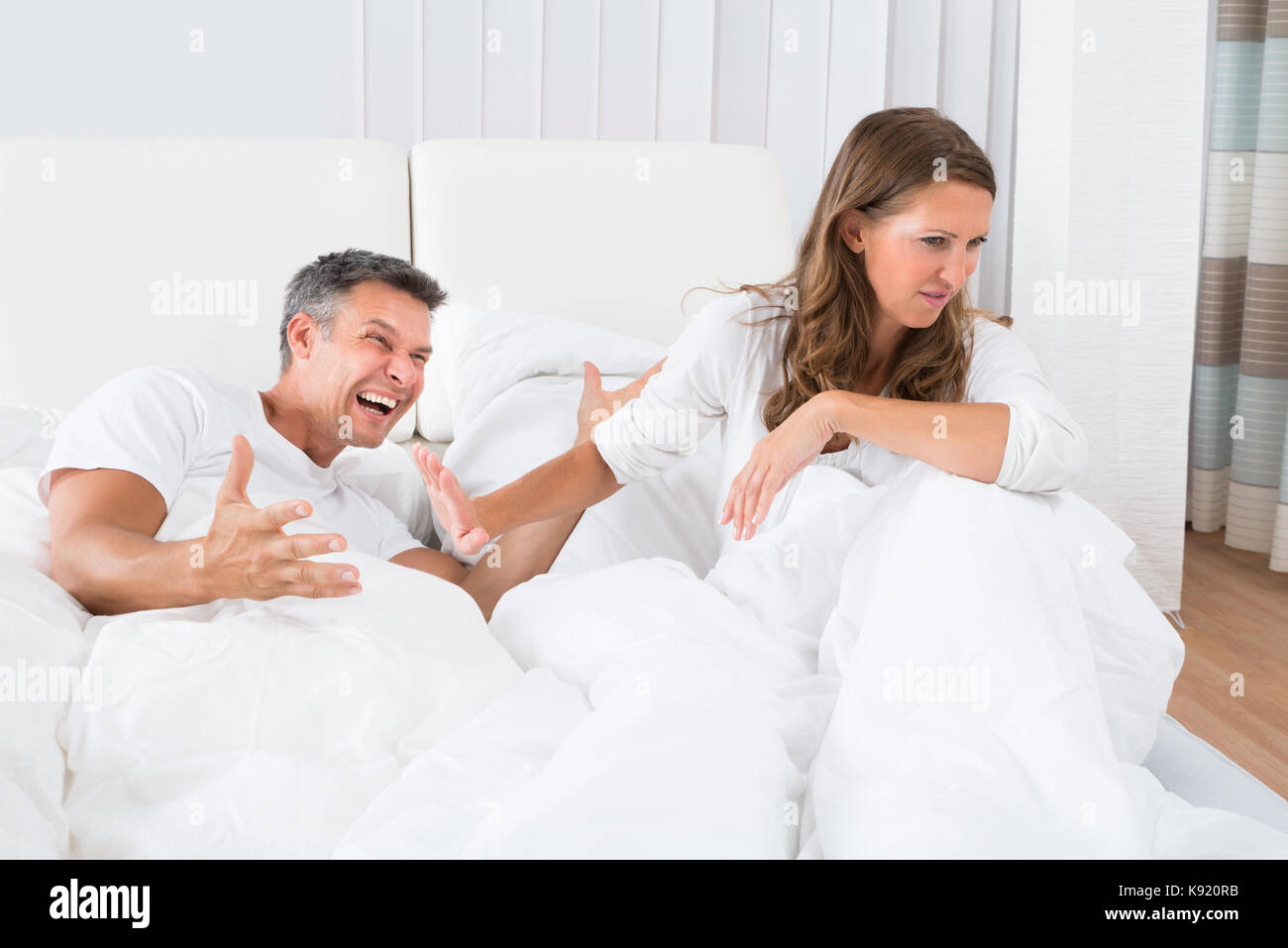 Portrait Of Unhappy Couple Disputing On Bed - Stock Image