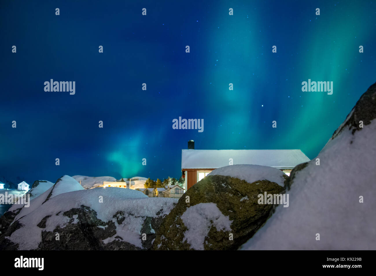 Norway. Lofoten. Winter Hamnoy. Northern lights above the roofs of houses - Stock Image