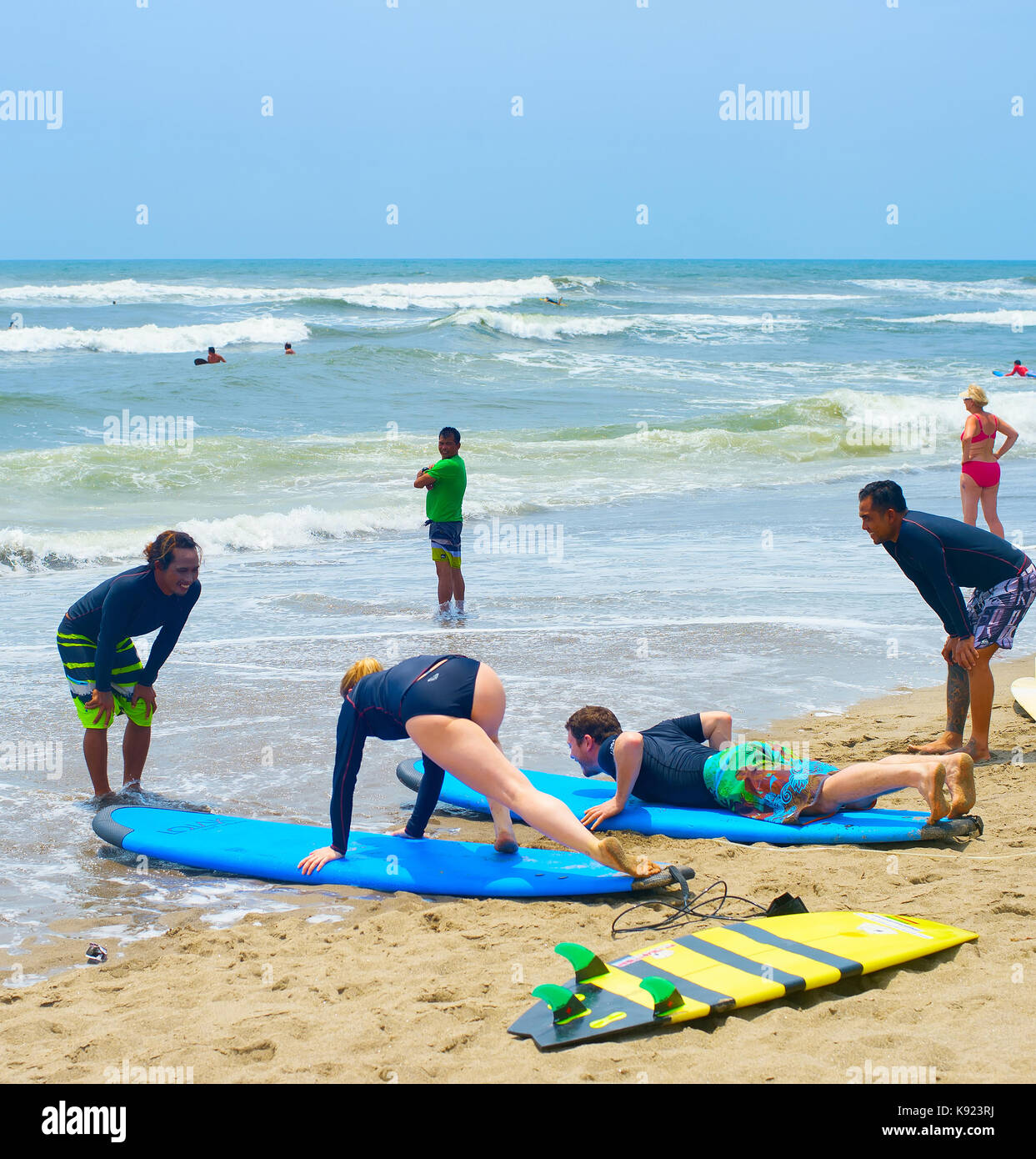 BALI ISLAND, INDONESIA - FEBRUARY 07, 2017: People learning surfing on the Balinese beach. Bali is the world famous - Stock Image
