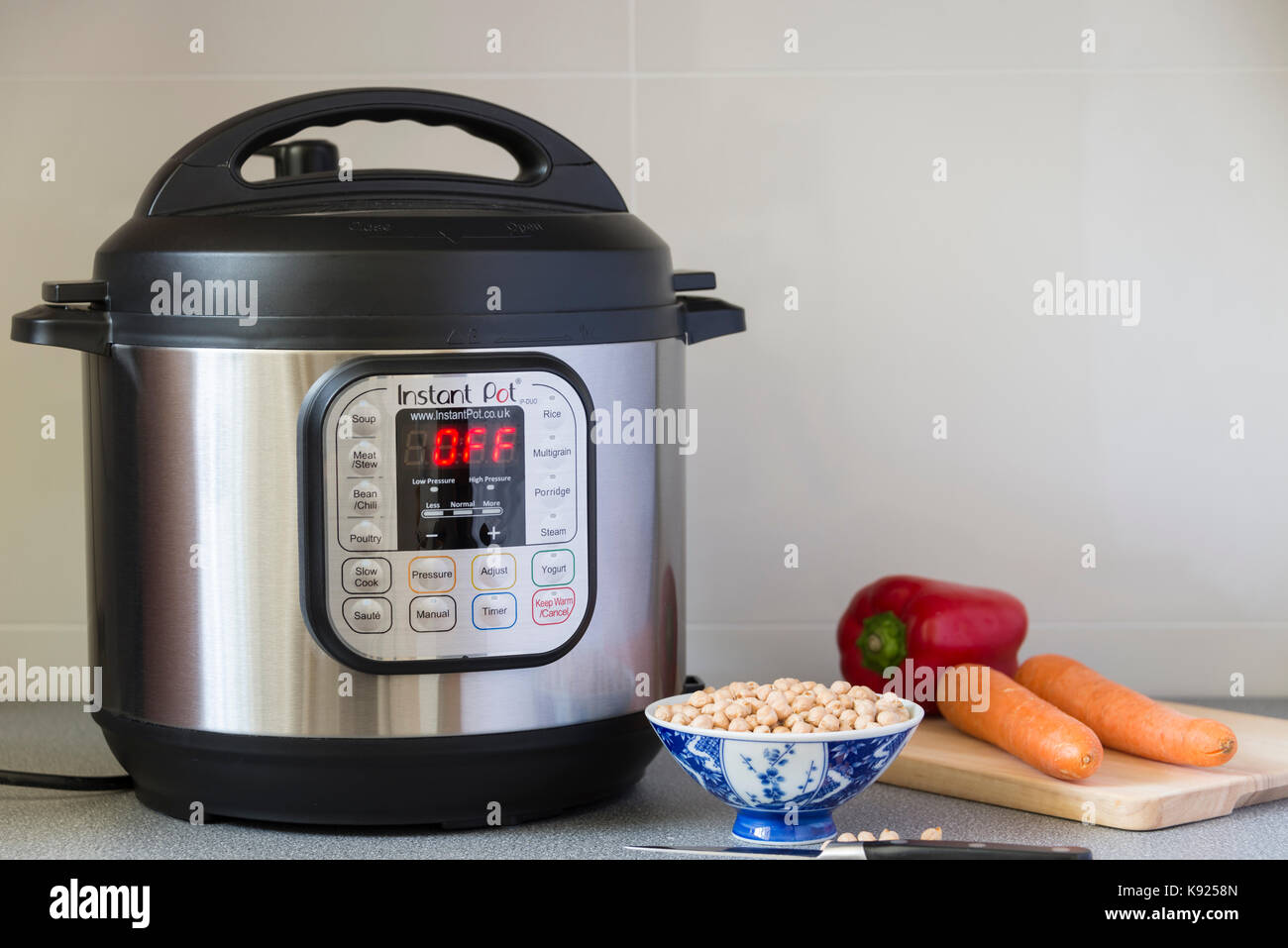 An Instant Pot Electric Pressure Cooker in use in a kitchen. - Stock Image