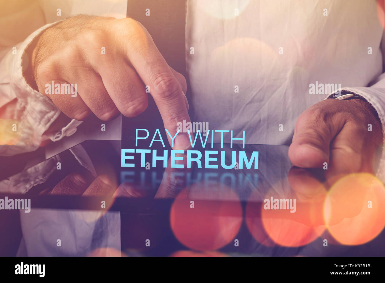 Pay with Ethereum cryptocurrency concept with businessman and digital tablet - Stock Image