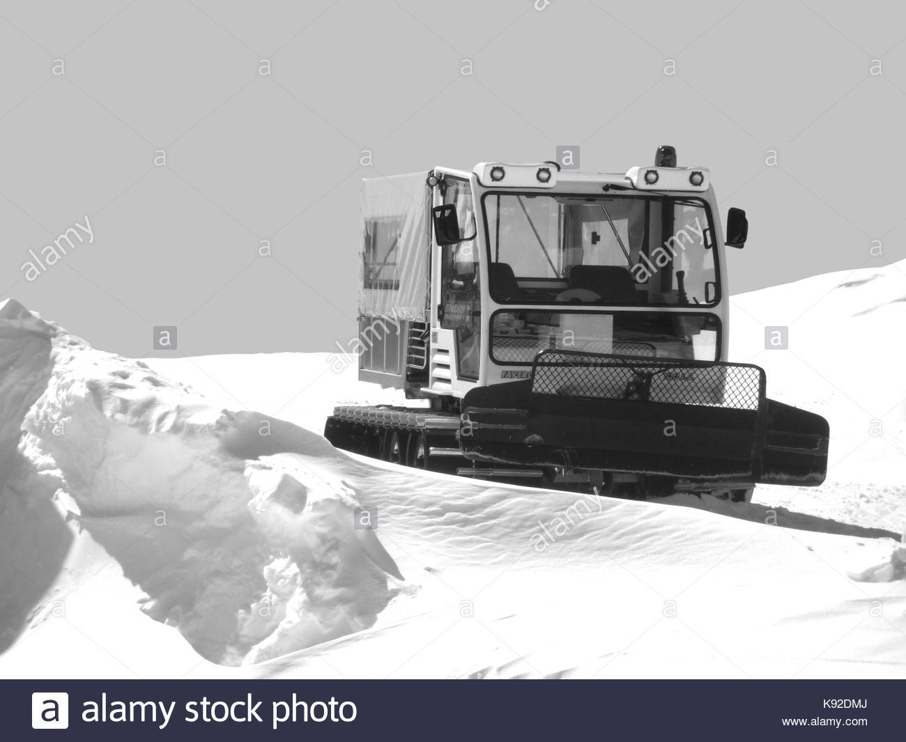 snowcat parked on a snowcapped territory - Stock Image