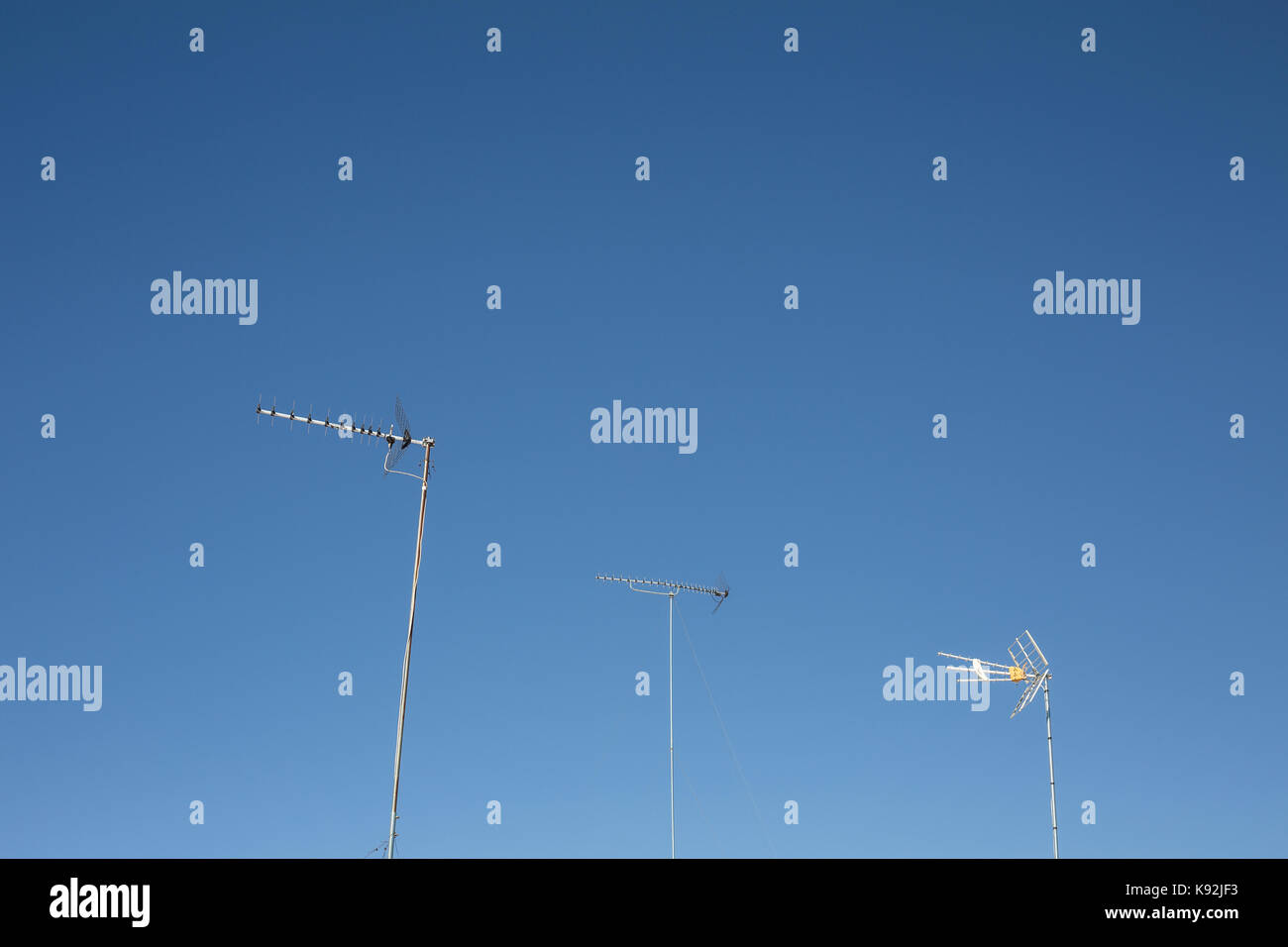 TV Aerial / Antenna masts against a blue sky. - Stock Image