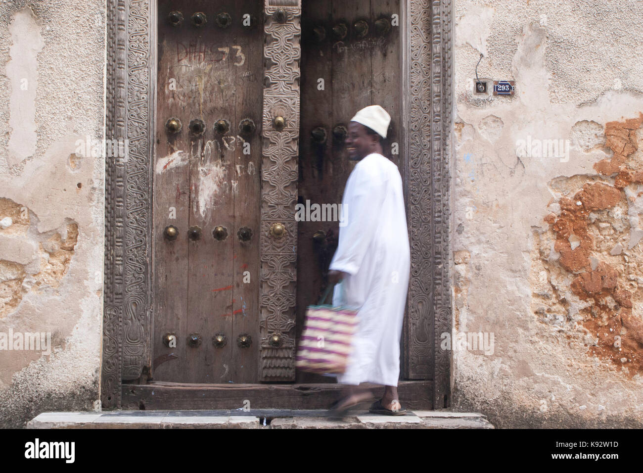 A man in traditional dress walking though an ornate carved wood door, Stone Town, Zanzibar, Tanzania, East Africa Stock Photo