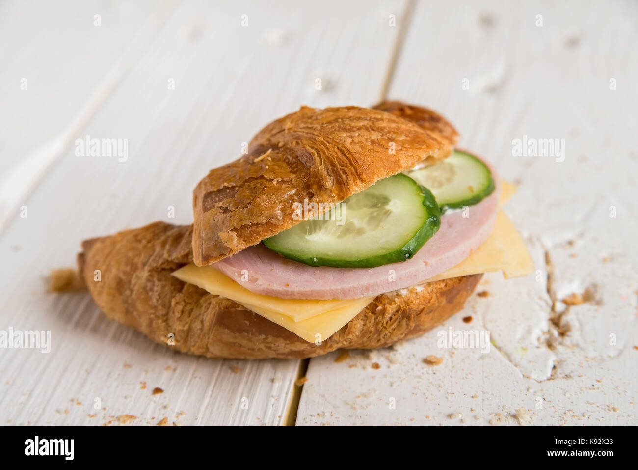 Croissant with ham, cheese and cucumber - Stock Image