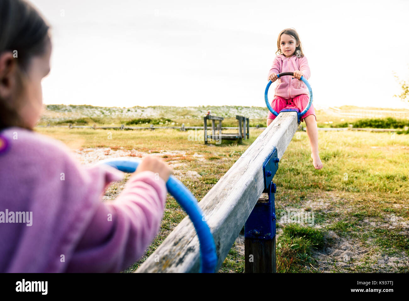 Little twin girls children are riding seesaw swing in park. Active children playing on teeter-tooter n a playground - Stock Image