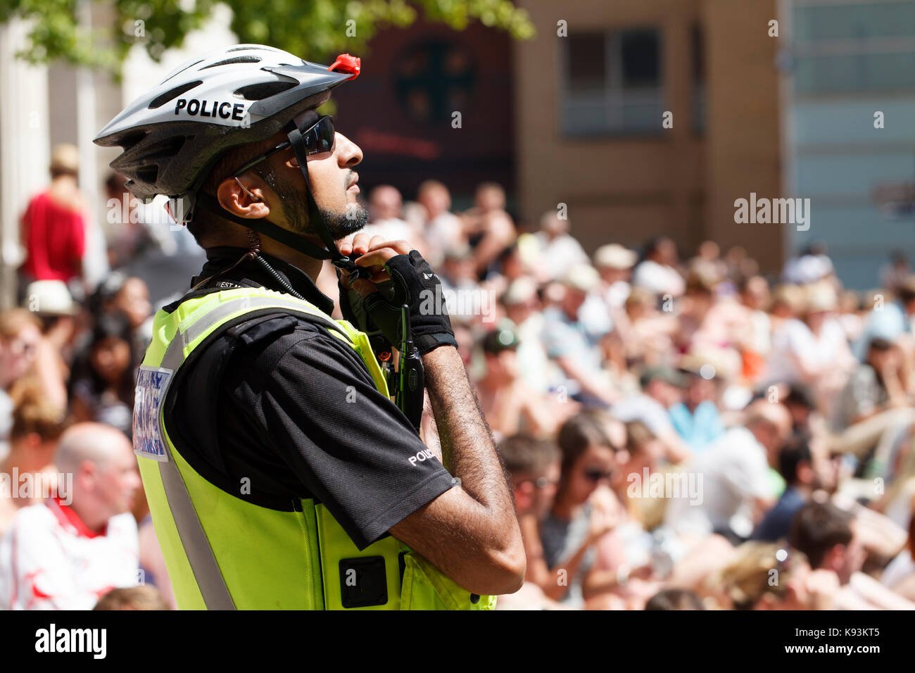 An Asian British Policeman adjusts his pedal cycle helmet in front of a large crowd a a event in central Birmingham, - Stock Image