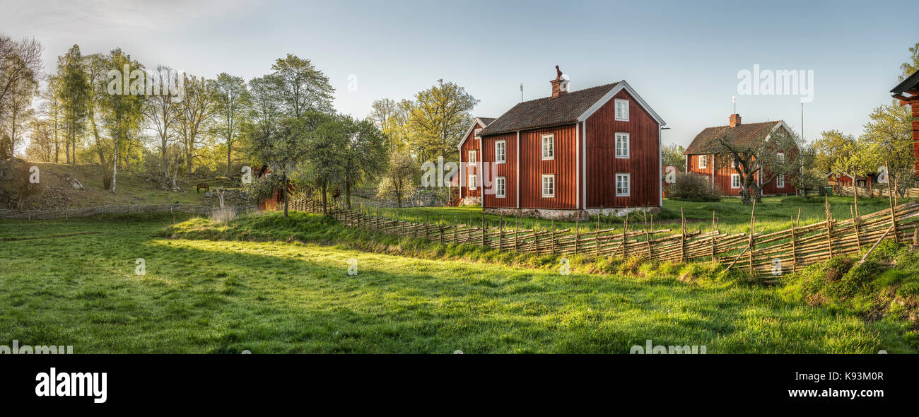 Old farm house and traditional roundpole fence in a rural landscape at the village Stensjo by in Smaland, Sweden, - Stock Image