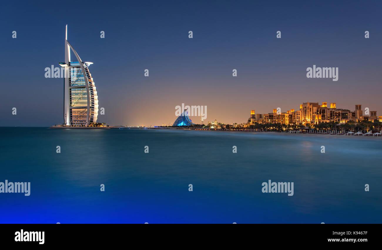 Cityscape of Dubai, United Arab Emirates at dusk, coastline of Persian Gulf with illuminated Burj Al Arab skyscraper - Stock Image