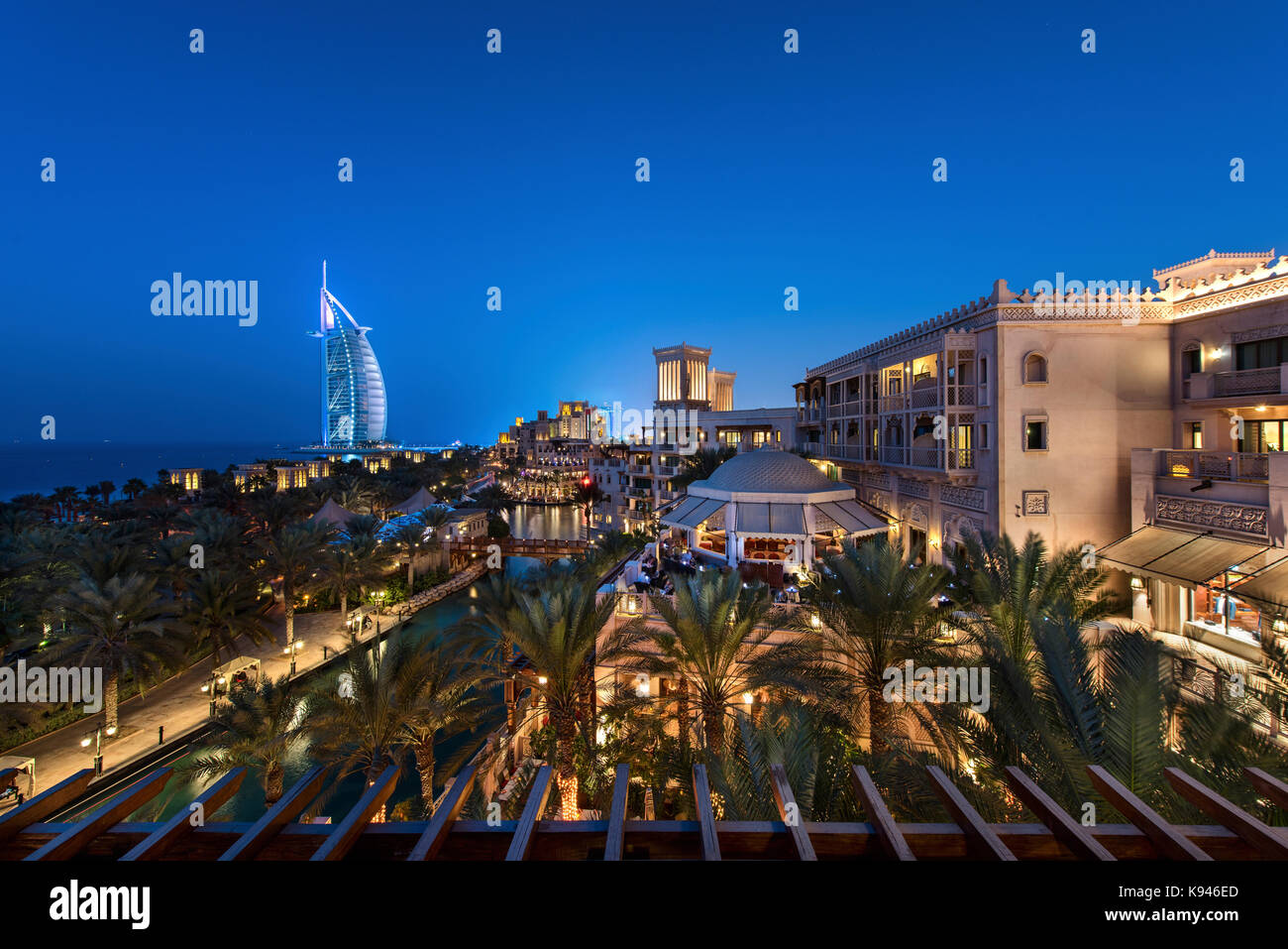 Cityscape of the Dubai, United Arab Emirates at dusk, with illuminated buildings and the Burj Al Arab in the distance. - Stock Image
