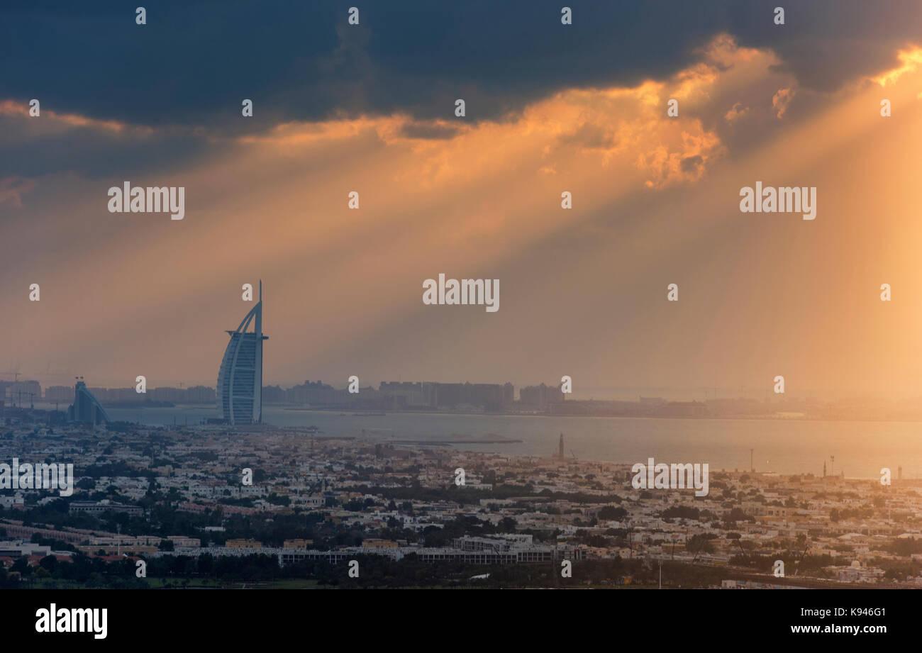 Cityscape of Dubai, United Arab Emirates at dusk with the Burj Al Arab skyscraper in the distance. - Stock Image