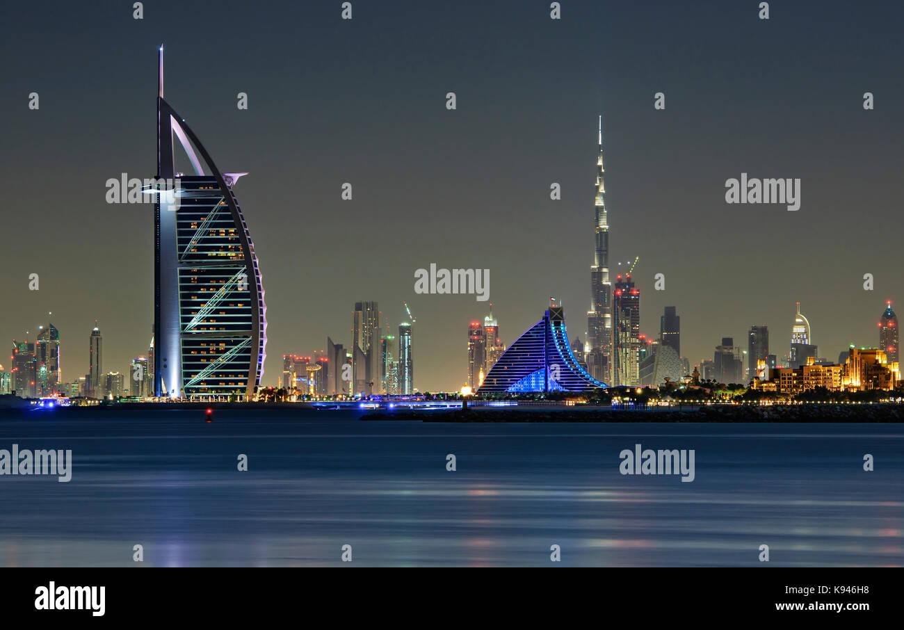 Cityscape of Dubai, United Arab Emirates at dusk, with illuminated Burj Khalifa and Burj Al Arab skyscrapers lining - Stock Image
