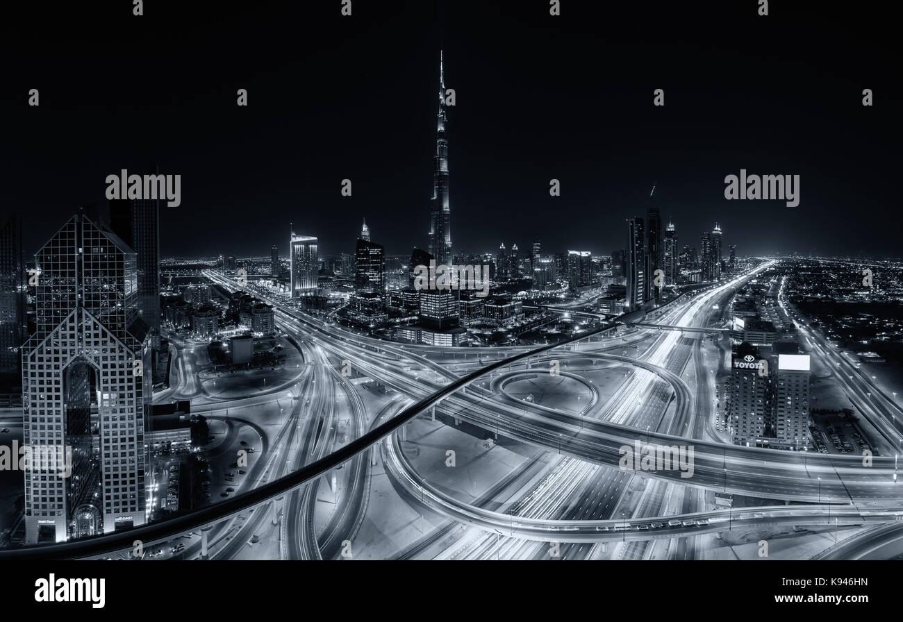 Cityscape of Dubai, United Arab Emirates at dusk, with the Burj Khalifa skyscraper and illuminated highways and - Stock Image