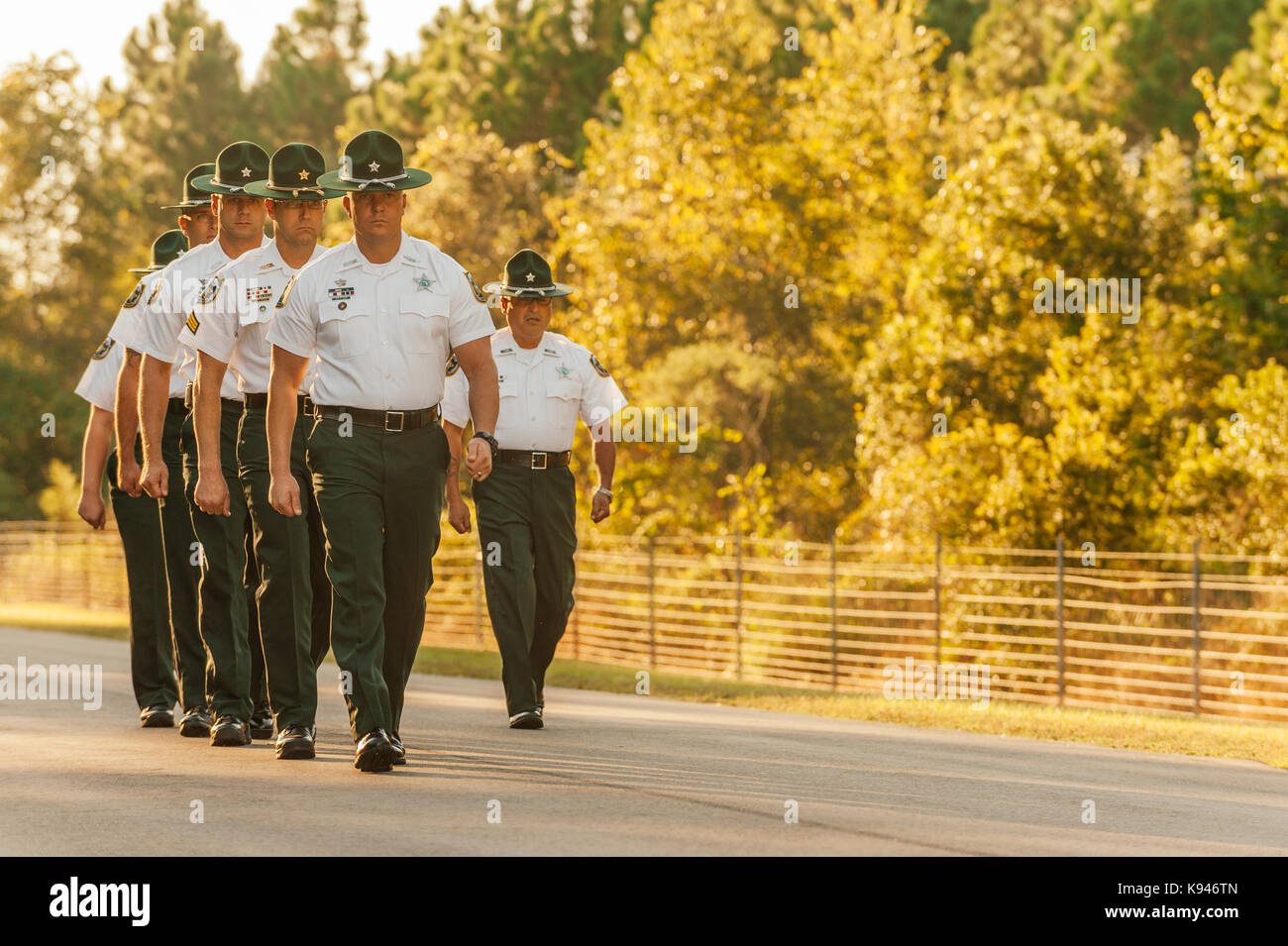The law enforcement training staff, or drill instructors, march in formation to greet a new police academy recruit - Stock Image