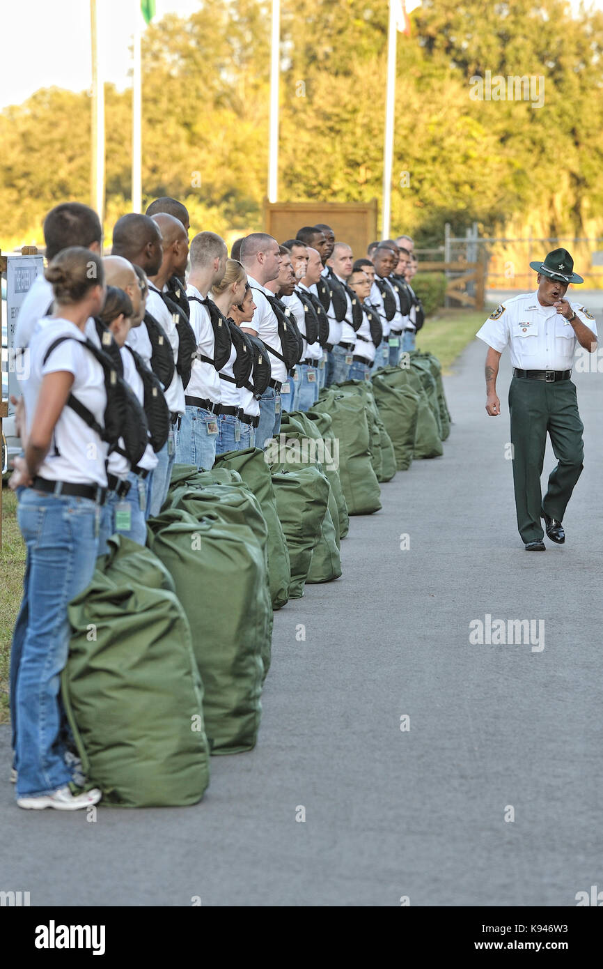 Law enforcement academy drill instructor gives instructions to a new police recruit class as they start their first - Stock Image
