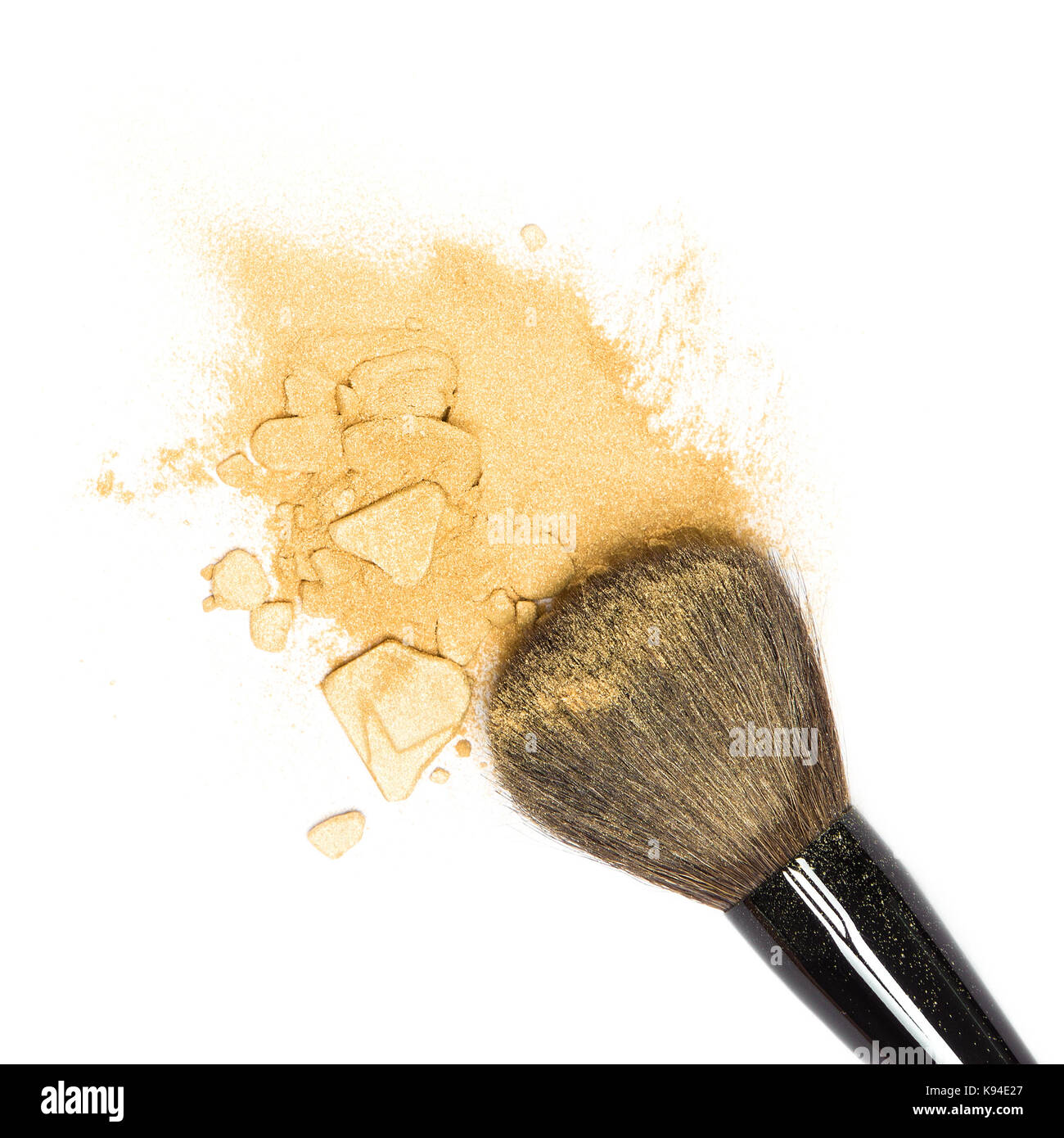 Close-up of crushed mineral shimmer powder golden color with makeup brush on white background - Stock Image