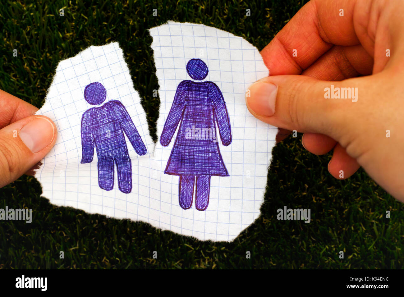 Woman hands ripping piece of paper with hand drawn man and woman figures. Grass background. Doodle style. - Stock Image