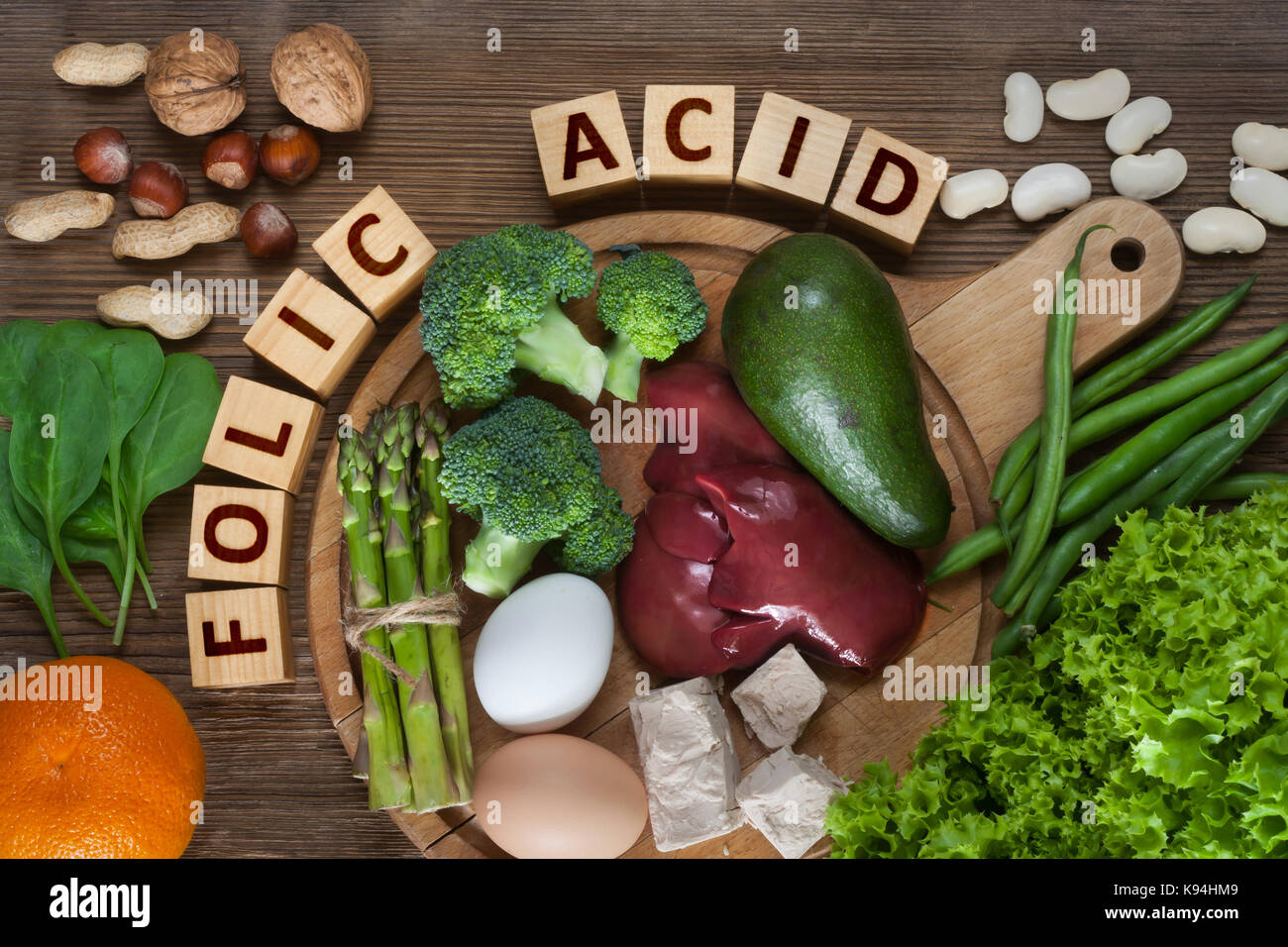 Natural sources of folic acid as liver, asparagus, broccoli, eggs, salad, avocado, yeast, nuts, spinach, orange - Stock Image