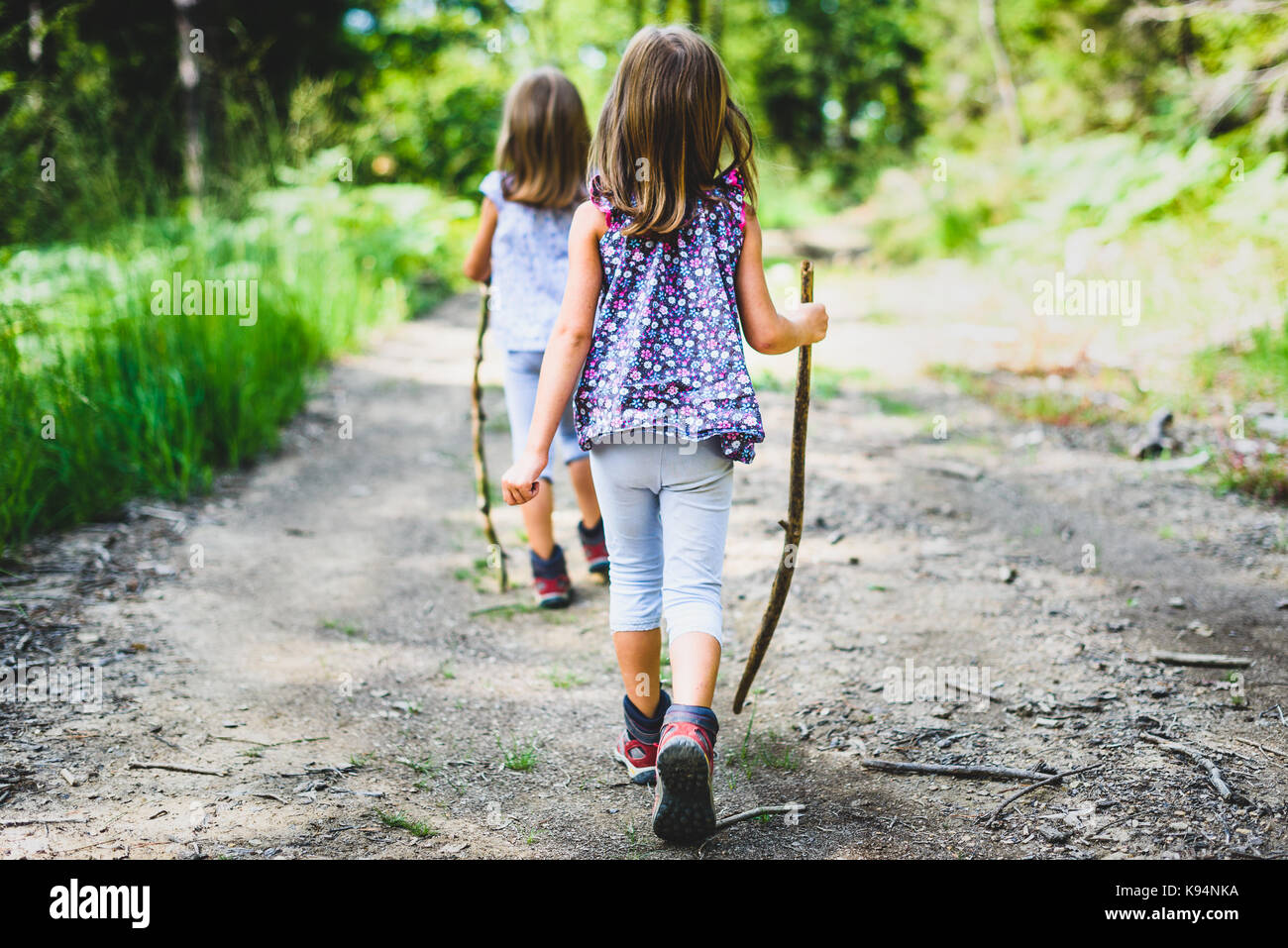 Children - twin girls are hiking in the mountains. Active family, parents and children mountaineering in the nature. - Stock Image